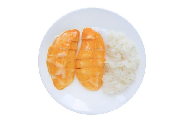 Zoete rijpe gouden mango en plakkerige rijst giet overgoten met kokosroom op witte cirkel keramische plaat geïsoleerd op een witte achtergrond.