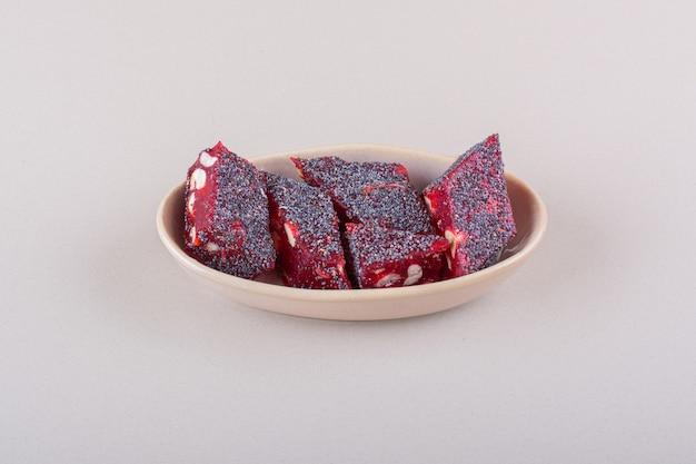 Zoete rode snoepjes met noten in beige kom op wit oppervlak. hoge kwaliteit foto