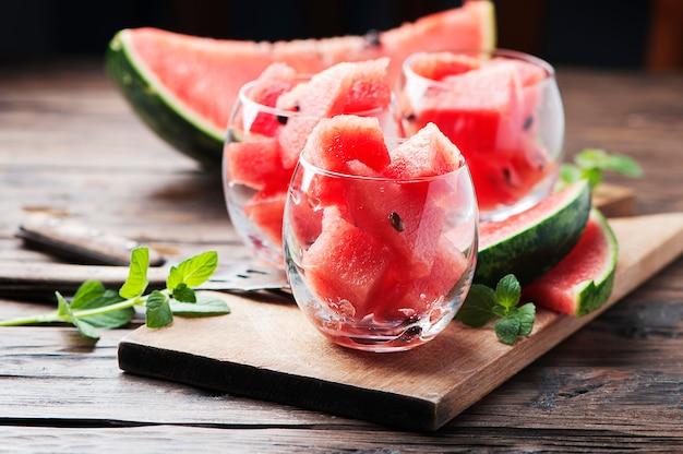 Zoete rode watermeloen en munt op de houten tafel