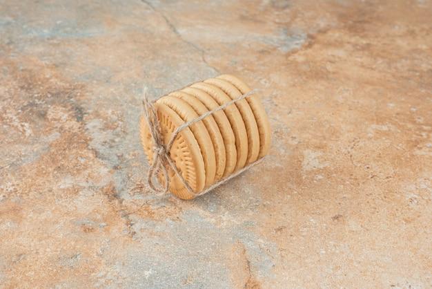 Zoete ronde koekjes in touw op marmeren achtergrond