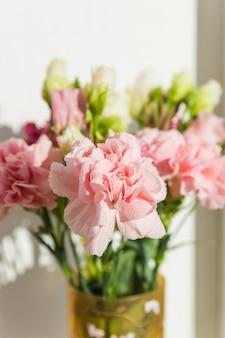 Zoete roze anjerbloemen in vaas op een witte achtergrond met tekstruimte. mooie verse bloeiende tedere anjers. moederdag, bedankt ontwerpconcept.