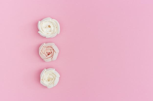 Zoete roze en witte marshmallows in de vorm van roze bloem op roze papier met kopie ruimte. vakantie achtergrond met kopie ruimte voor valentijnsdag. hou van concept.