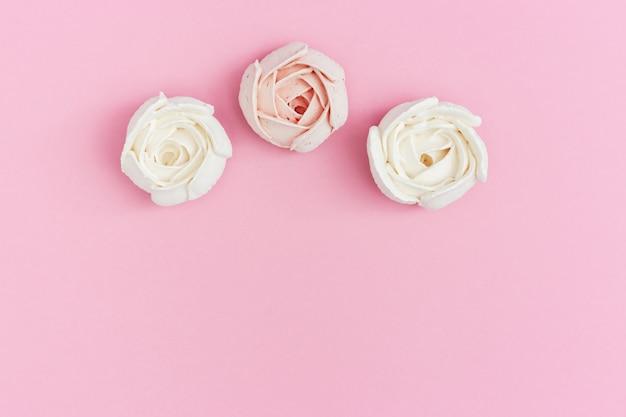 Zoete roze en witte marshmallows in vorm van roze bloem op roze papier met kopie ruimte. vakantieachtergrond met exemplaarruimte voor valentijnsdag. liefde concept.