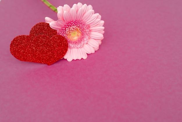 Zoete roze gerberabloem voor liefde romantische achtergrond met hart. zachte selectieve aandacht. kopieer ruimte.