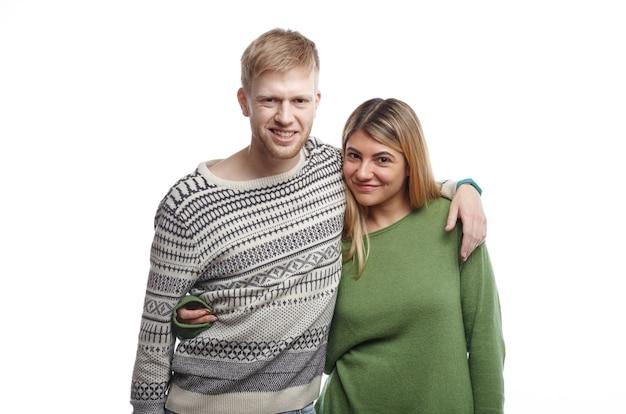 Zoete schattige romantische jonge europese man en vrouw die gelukkig glimlachen en elkaar knuffelen
