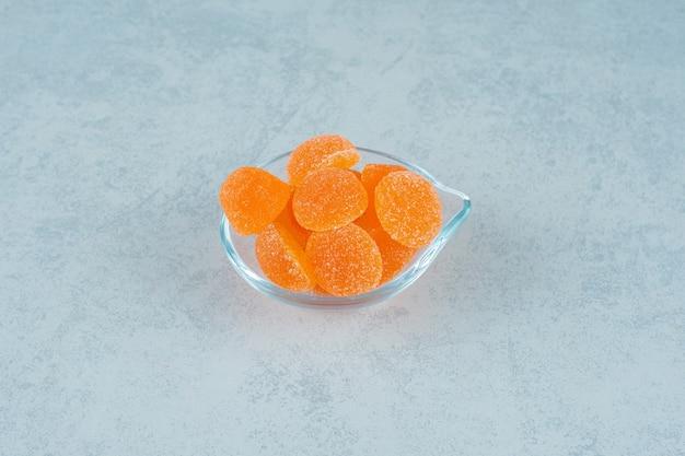 Zoete sinaasappelgeleisuikergoed met suiker in een glasplaat op een wit oppervlak