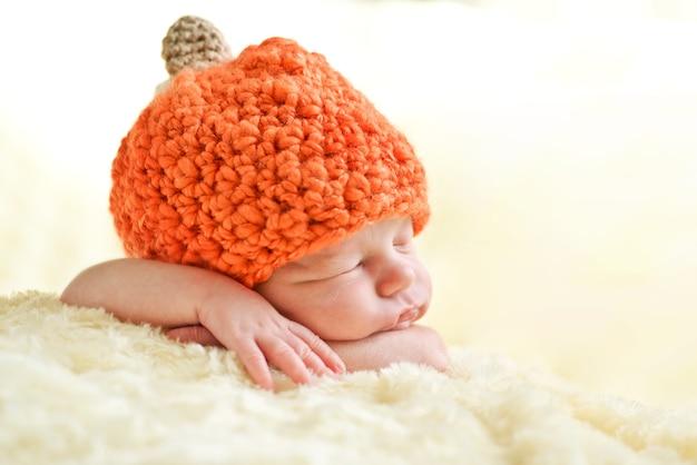 Zoete slapende pasgeboren baby die pompoenhoed draagt