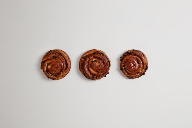 Zoete smakelijke broodjesbroodjes met rozijnen die op witte achtergrond worden geïsoleerd. vers gebakken dessert voor zoetekauw uit bakkerijhuis. zoetwaren. calorierijk voedselconcept. deense kaneel