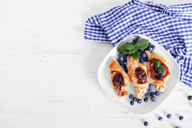 Zoete smakelijke gebakjes en verse bosbessen op plaat, bovenaanzicht
