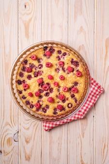 Zoete smakelijke taart met gelei en verse frambozenvruchten in ovenschaal met rode tafelkleedhanddoek