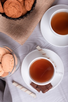 Zoete snacks, kopje thee op lichte achtergrond