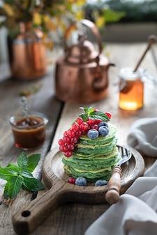Zoete spinazie pannenkoeken met krenten en bosbessen en honing.