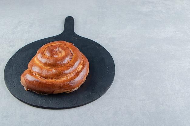 Zoete swirl broodje op een houten bord.