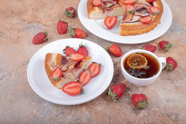 Zoete taart met aardbeien in een witte plaat met een kopje thee