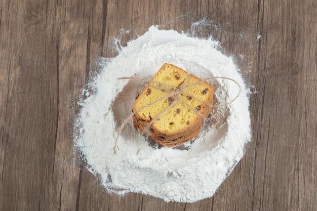 Zoete taart met ingrediënten op houten tafel.