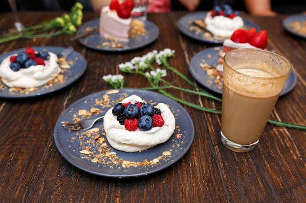 Zoete taarten met zomer bessen op een houten tafel. feest, zoete tafel. zomeraanbieding desserts in het restaurant.