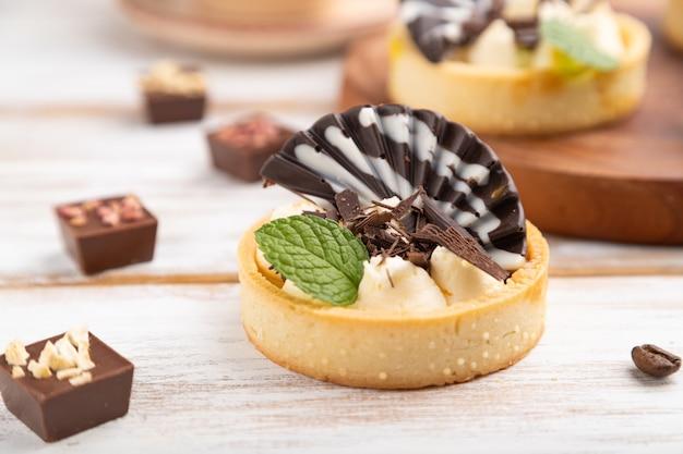 Zoete taartjes met chocolade en kaasroom met kopje koffie op een witte houten achtergrond en linnen textiel. zijaanzicht, close-up, selectieve aandacht.