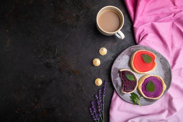 Zoete taartjes met gelei en melkroom met kopje koffie o