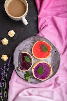 Zoete taartjes met gelei en melkroom met kopje koffie op een zwarte betonnen ondergrond en roze textiel