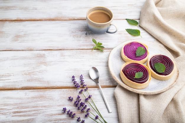 Zoete taartjes met gelei en melkroom met kopje koffie