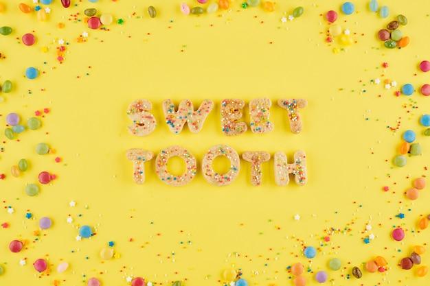 Zoete tand inscriptie gemaakt van suikerkoekjes op gele achtergrond, versierd met heldere hagelslag