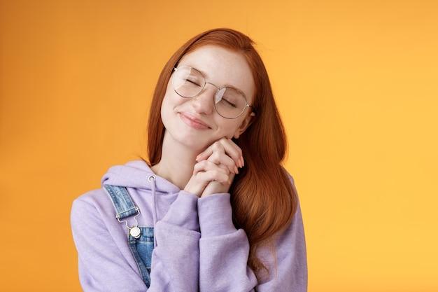Zoete tedere gelukkige romantische roodharige vriendin sluit ogen glimlachen dromerige beeldvorming mooie scène dagdromen pers palmen wangen dom herinnerend aan mooie herinneringen, staande oranje achtergrond ontspannen