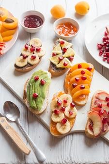 Zoete toast met jam en verschillende soorten fruit, abrikozen, perziken, bananen, sinaasappels en avocado versierd met granaatappels erop.