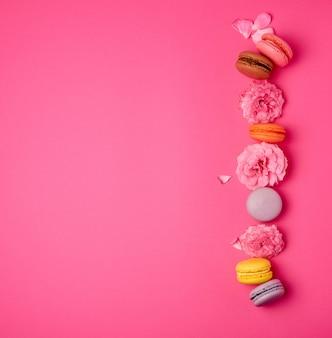 Zoete veelkleurige macarons met crème en een roze rozenknop