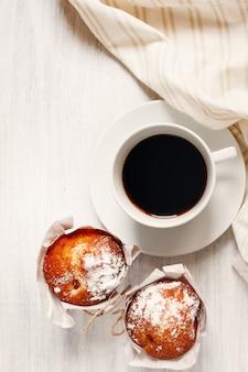 Zoete vers gebakken muffins met kopje koffie