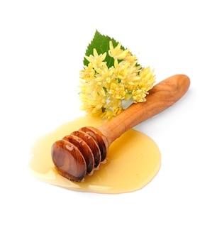 Zoete vloeibare honing met de bloem van de taklinde die op wit wordt geïsoleerd