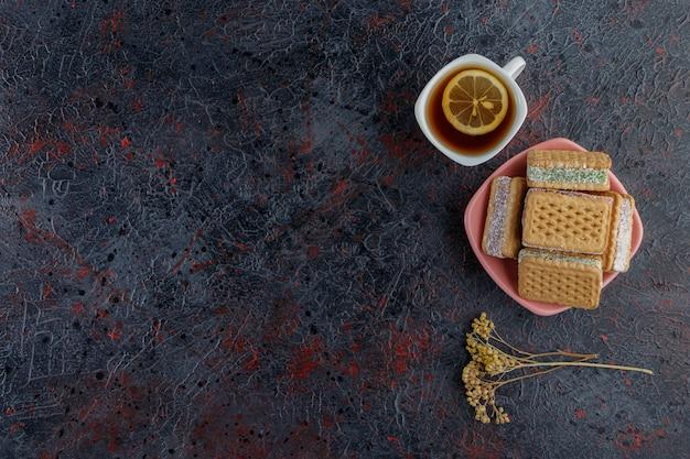 Zoete wafels met een witte kop hete thee en mimosabloem