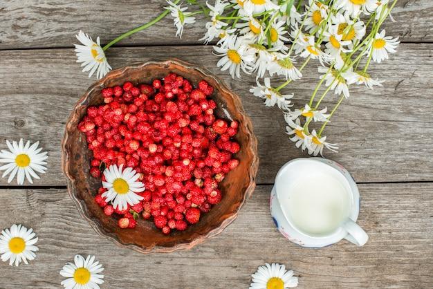 Zoete wilde aardbeien in plaat met kamille en melk op houten muur, bovenaanzicht.