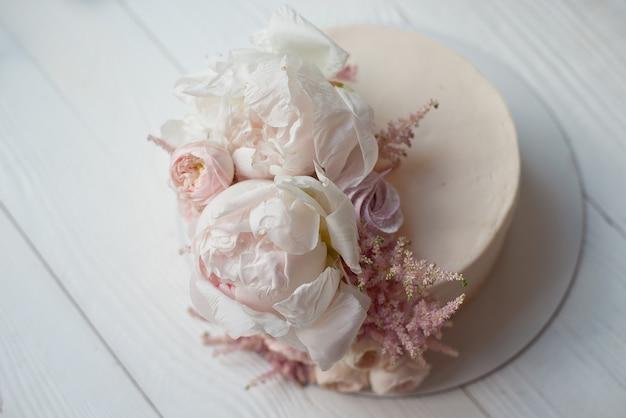Zoete witte slagroomtaart rond met roze rozen bloemen en witte pioen bovenop