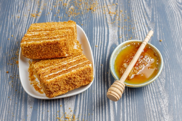 Zoete zelfgemaakte gelaagde honingcake met kruiden en noten.