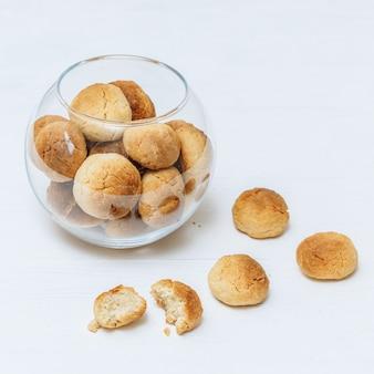 Zoete zelfgemaakte koekjes in glazen kom op witte achtergrond, close-up