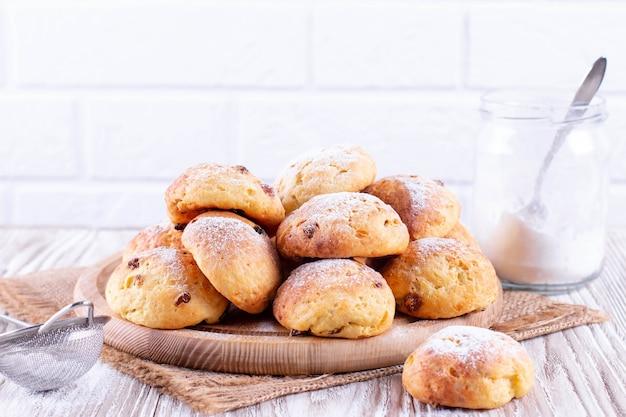 Zoete zelfgemaakte kwarkbroodjes met rozijnen en poedersuiker op een witte tafel