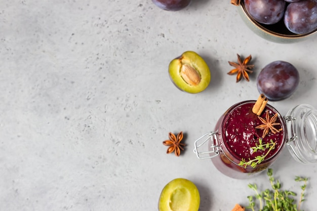 Zoete zelfgemaakte pittige pruimenjam, fruit, tijm en kruiden op grijze stenen tafel