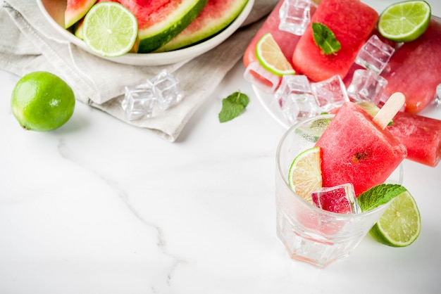Zoete zomer watermeloen en limoen ijslollys met gesneden watermeloen en munt, op wit marmeren oppervlak