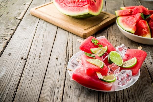 Zoete zomer watermeloen en limoen ijslollys met gesneden watermeloen en munt