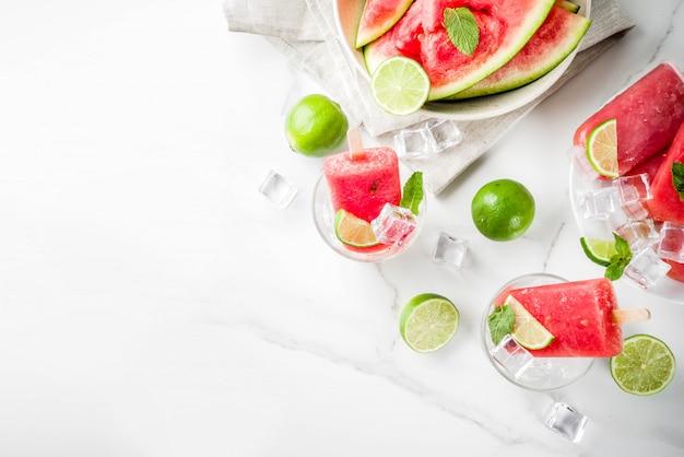 Zoete zomer watermeloen en limoen ijslollys met gesneden watermeloen