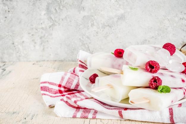 Zoete zomerdesserts, zelfgemaakte organische ijsijsjes van framboos en yoghurt