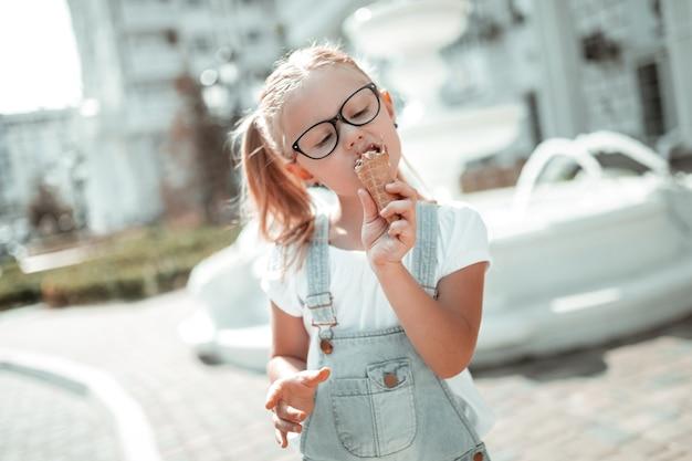Zoetekauw. geconcentreerd meisje dat geniet van haar ijshoorntje dat ervan eet en haar ogen sluit in de zomer.