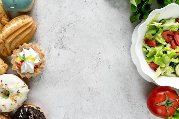Zoetwarenvoedsel en gezonde plantaardige salade op ruwe oppervlakte