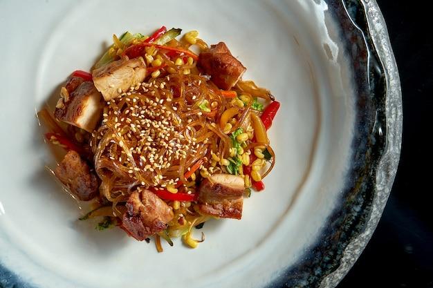 Zoetzure glasnoedels met varkensvlees, groenten en uien, geserveerd in een witte kom.