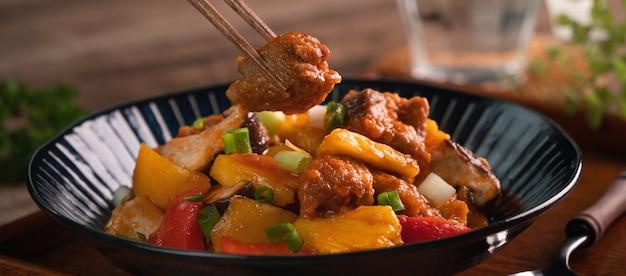 Zoetzure sauced gefrituurd varkensvlees met gehakte peper en ananas in een blauw bord op houten tafel