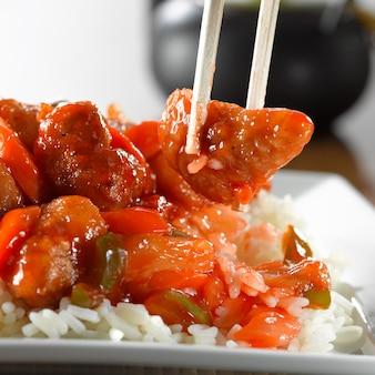 Zoetzure varkensvlees op rijst die met eetstokjes wordt gegeten
