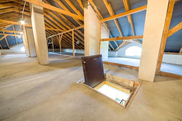 Zolder van een gebouw met houten balken van een dakconstructie en een branddeur in de vloer.