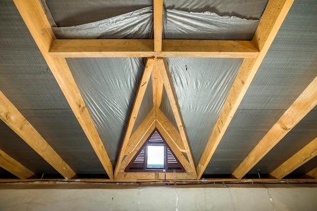 Zolder van een gebouw met houten balken van een dakstructuur en een klein venster.