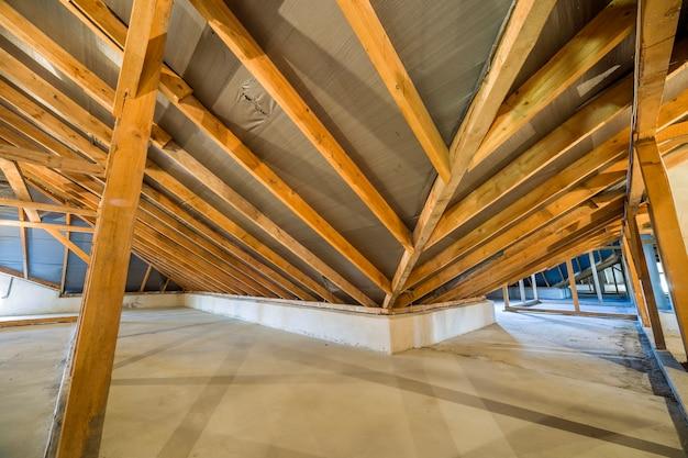 Zolder van een gebouw met houten balken van een dakstructuur.