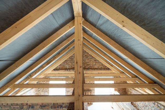 Zolderruimte van een gebouw in aanbouw met houten balken van een dakconstructie en bakstenen muren.